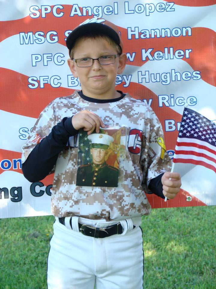Tannar Patterson holding a picture of his cousin, LCpl Alec Terwiske